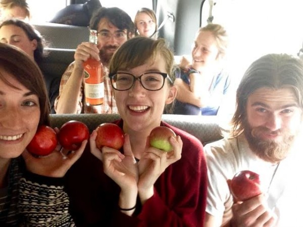 Image of several students in van seats, including Claire Jordy, who sits at the center and has light brown hair and glasses. The students in the front row smile and hold apples up by their faces. One boy in the middle row holds up an orange beverage in a class container.