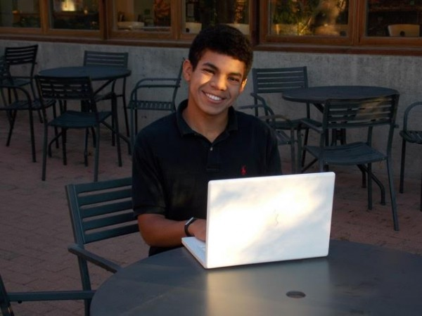 Image of Emmanuel Greeno, a boy with light brown skin and dark hair, smiling and sitting at a cafe table typing on an Apple laptop.