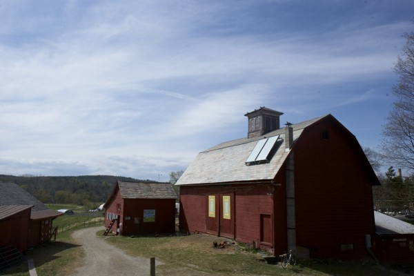 Image of a red barn under a blue sky with sweeping white clouds.