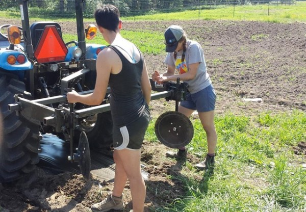 Image of two students repairing a tractor outside a plowed field. The student to the left has short-cropped hair and wears a black tank top and shorts. The student to the right has braids and wears a tan-and-blue baseball cap, grey T-shirt, blue shorts, and boots.