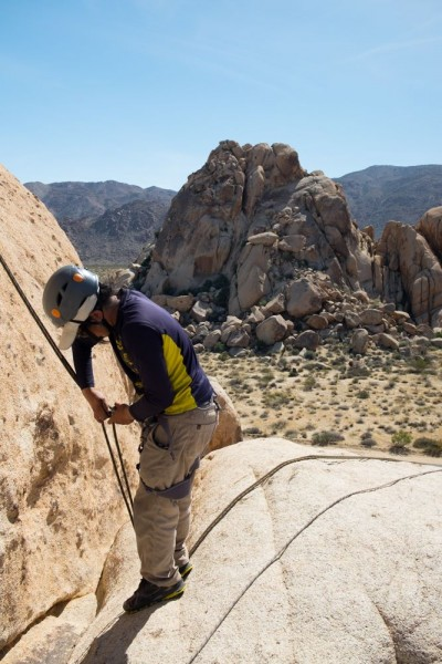 Image of a male student rigging his rappel with desert shrubbery and large rock mountains in the background. The student wears a blue long-sleeved shirt, khakis, and a grey helmet, and looks away from the camera to focus on the rappel.