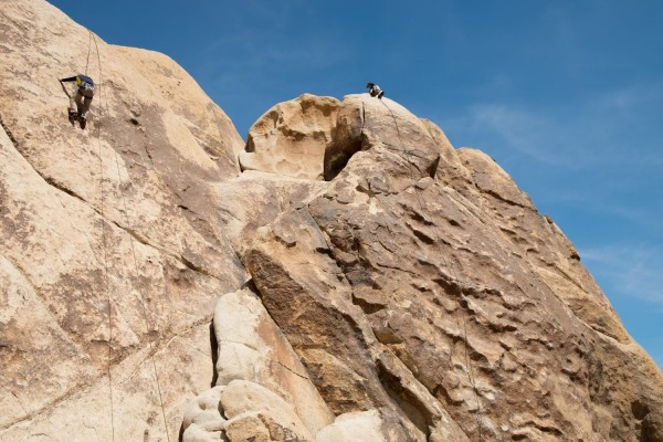 Image of Andew and another student scaling a rock face in Joshua Tree National Park as part of their outdoor adventure experience. One student climbs on a rope, while the other rests at the top of a rock. The two students can barely be identified on the massive rocks.