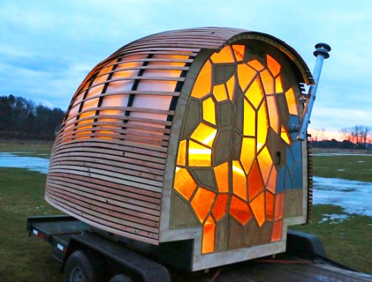 "Image of a wheeled ""tiny house"" with an exterior made of warm-colored stained glass. The house sits on a trailer bed in a grassy field with some remains of snow at sunset."