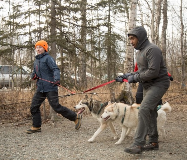 Image of two students learning to mush husky dogs on a forest trail. The student to the left has pale skin, an orange hat, blue coat, and black pants. The student to the right has dark skin, wears a hooded grey jacket, and long grey pants.
