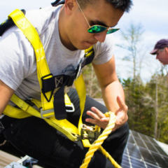 Image of a male student from College of the Atlantic installing solar panels. He has short brown hair and wears sunglasses, a grey T-shirt, and a yellow safety harness. He clutches a yellow rope in one hand.