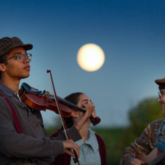 Image of Dickinson students Max Jacobs, Gaby Corcoran, and Alexander Dillan standing in front of a full moon on the farm. Max is playing a violin. Gaby and Alexander are laughing at each other as if in the middle of a joke as Alexander plays the guitar.