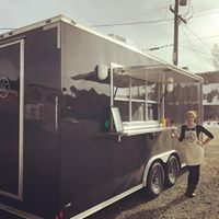 Image of Kara Kessler, a white woman with light brown hair, standing outside a black vegan food truck on a dirt road. She wears a black long sleeve shirt and pants and a white apron, and puts her right hand on her hip.