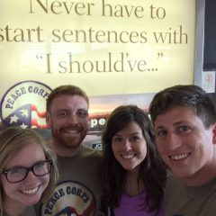 "Image of Travis Sherlin standing with two female and another male student, all of whom are smiling. They are standing in front of a Peace Corps sign that says ""Never have to start sentences with 'I should've'...""."