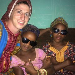 Image of Travis Sherlin, a white boy with short-cropped brown hair, sitting with two dark-skinned girls with sunglasses. The three are wearing colorful robes and smiling and posing for the camera. Travis wears a red head covering, and the two girls next to him wear brown rounded caps.