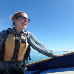 Image of Heather Sieger, a marine biology student from College of the Atlantic, smiling while riding on a boat. She has blond hair and light-colored skin, and wears sunglasses, a yellow life jacket, and a plaid jacket.