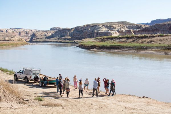 Image of a group of about a dozen young people standing in a circle next to a rowboat hooked to a white truck on a dusty road. In the background are a long river, a grassy bank, and several rock formations.