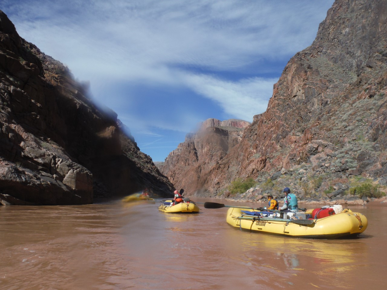 """Image of two yellow rafts, each with two students, floating down a reddish-brown river. In the background are two tall rock formations whose sides form a """"V""""; in the center of the V is a blue sky."""