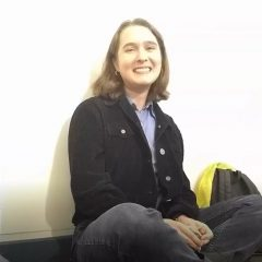 Image of Leigh Rankin, a young white woman with short brown hair, a black jacket, blue shirt, and grey pants, sitting cross-legged up against a white wall and laughing.